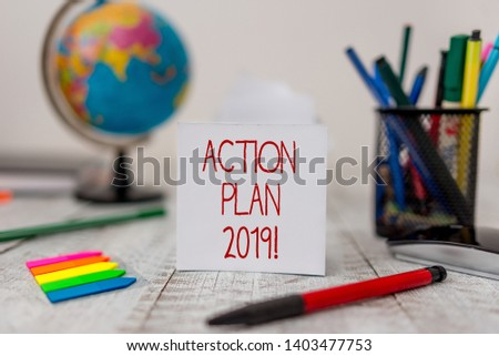 Text sign showing Action Plan 2019. Conceptual photo proposed strategy or course of actions for current year Stationary and paper sheets plus small arrows with globe on the wooden desk.