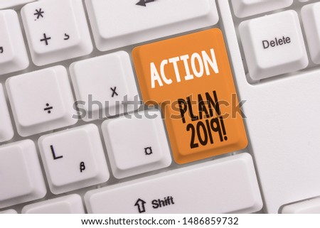 Text sign showing Action Plan 2019. Conceptual photo proposed strategy or course of actions for current year White pc keyboard with empty note paper above white background key copy space.