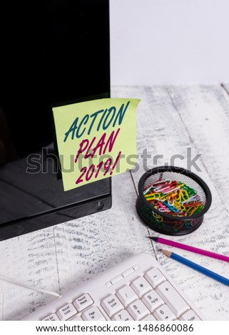 Text sign showing Action Plan 2019. Conceptual photo proposed strategy or course of actions for current year Note paper taped to black computer screen near keyboard and stationary.