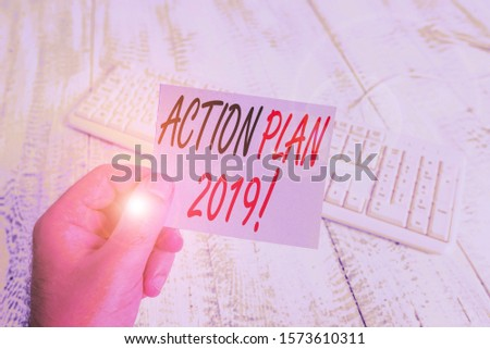 Text sign showing Action Plan 2019. Conceptual photo proposed strategy or course of actions for current year man holding colorful reminder square shaped paper white keyboard wood floor. #1573610311