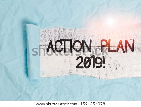 Text sign showing Action Plan 2019. Conceptual photo proposed strategy or course of actions for current year Cardboard which is torn in the middle placed above a wooden classic table.