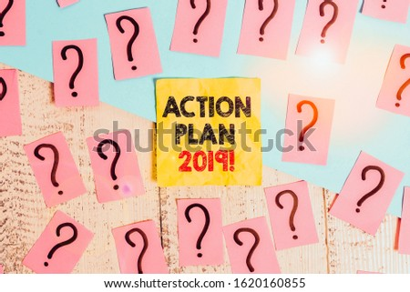 Text sign showing Action Plan 2019. Conceptual photo proposed strategy or course of actions for current year Scribbled and crumbling papers with thick cardboard above wooden table.