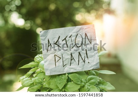 Text sign showing Action Plan. Conceptual photo proposed strategy or course of actions for certain time Plain empty paper attached to a stick and placed in the green leafy plants.