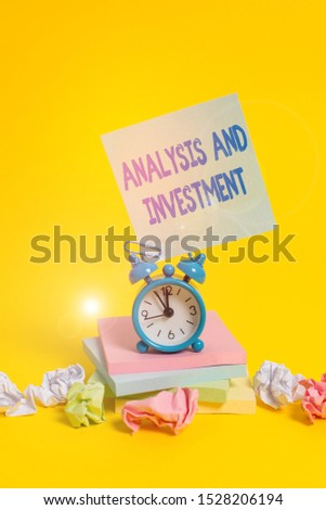 Text sign showing Analysis And Investment. Conceptual photo studying market then do business in large scale Alarm clock sticky note paper balls stacked notepads colored background.