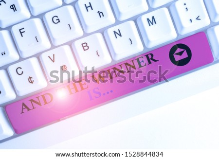 Text sign showing And The Winner Is. Conceptual photo announcing a demonstrating or thing that wins something White pc keyboard with empty note paper above white background key copy space.