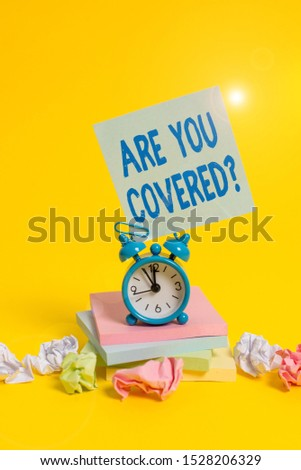 Text sign showing Are You Covered Question. Conceptual photo asking someone or patient if he have insurance Alarm clock sticky note paper balls stacked notepads colored background.