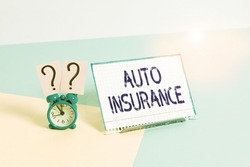 Text sign showing Auto Insurance. Conceptual photo mitigate costs associated with getting into an auto accident Mini size alarm clock beside a Paper sheet placed tilted on pastel backdrop.