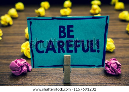 Text sign showing Be Careful. Conceptual photo making sure of avoiding potential danger mishap or harm Clothespin holding blue paper note crumpled papers several tries mistakes. #1157691202