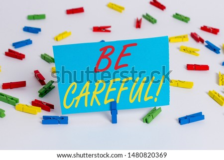 Text sign showing Be Careful. Conceptual photo making sure of avoiding potential danger mishap or harm Colored clothespin papers empty reminder white floor background office. #1480820369