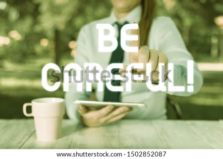 Text sign showing Be Careful. Conceptual photo making sure of avoiding potential danger mishap or harm Female business person sitting by table and holding mobile phone. #1502852087