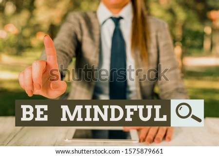 Text sign showing Be Mindful. Conceptual photo paying close attention to or being conscious of something Female business person sitting by table holding mobile phone. #1575879661