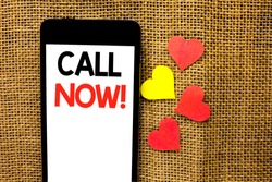 Text sign showing Call Now. Conceptual photo Contact Talk Chat Hotline Support Telephony Customer Service written on Cardboard Piece Holding By Sculpture on the jute background.