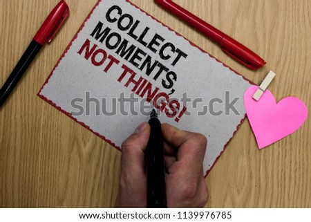 Text sign showing Collect Moments, Not Things. Conceptual photo Happiness philosophy enjoy simple life facts Written sticky note clip pinch heart hand hold marker red pen on wooden desk. #1139976785