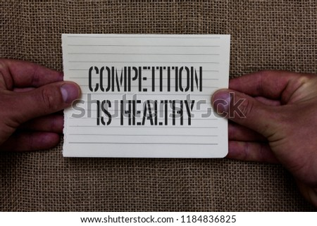 Text sign showing Competition Is Healthy. Conceptual photo Rivalry is good in any Venture leads to Improvement Man holding piece notebook paper jute background Communicating ideas. #1184836825