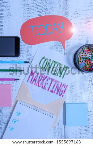 Text sign showing Content Marketing. Conceptual photo involves creation and sharing of online material Envelop speech bubble smartphone sheet pens spiral notepads clips wooden.