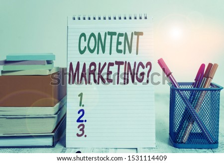 Text sign showing Content Marketing Question. Conceptual photo involves creation and sharing of online material Pens metal holder stacked note pads books square box spiral wooden table. #1531114409