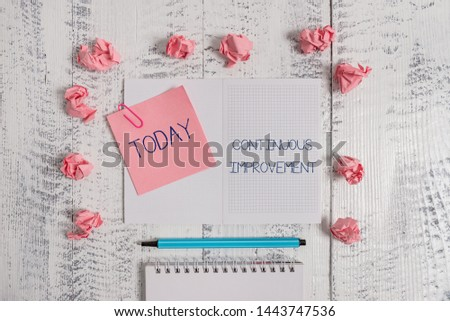 Text sign showing Continuous Improvement. Conceptual photo ongoing effort to improve products or processes Squared spiral notepad clip note highlighter paper balls wooden background.