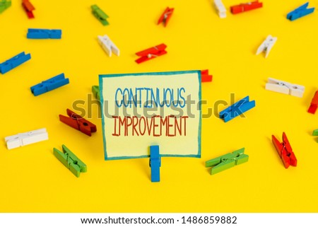 Text sign showing Continuous Improvement. Conceptual photo ongoing effort to improve products or processes Colored clothespin papers empty reminder yellow floor background office.