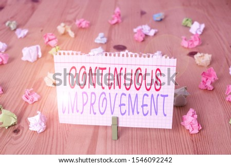 Text sign showing Continuous Improvement. Conceptual photo ongoing effort to improve products or processes Colored crumpled papers empty reminder wooden floor background clothespin.