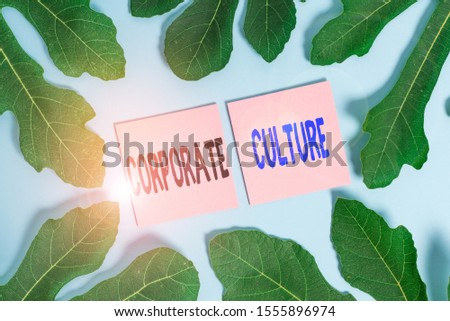 Text sign showing Corporate Culture. Conceptual photo pervasive values and attitudes that characterize a company Leaves surrounding notepaper above an empty soft pastel table as background.
