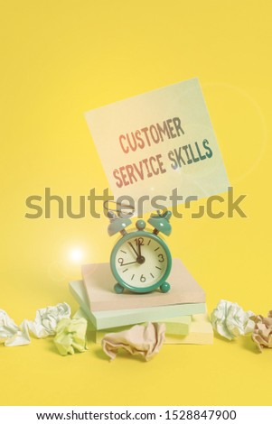 Text sign showing Customer Service Skills. Conceptual photo Aptitude to master to improve dealings with client Alarm clock sticky note paper balls stacked notepads colored background.
