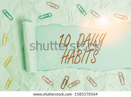 Text sign showing 10 Daily Habits. Conceptual photo Healthy routine lifestyle Good nutrition Exercises Paper clip and torn cardboard placed above a plain pastel table backdrop.