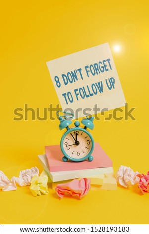 Text sign showing 8 Don T Forget To Follow Up. Conceptual photo asking someone to keep connection with others Alarm clock sticky note paper balls stacked notepads colored background.