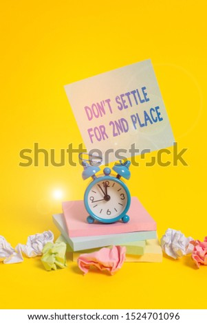 Text sign showing Don T Settle For 2Nd Place. Conceptual photo you can be the first dont stop here Alarm clock sticky note paper balls stacked notepads colored background.