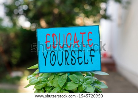 Text sign showing Educate Yourself. Conceptual photo prepare oneself or someone in a particular area or subject Plain empty paper attached to a stick and placed in the green leafy plants. #1545720950