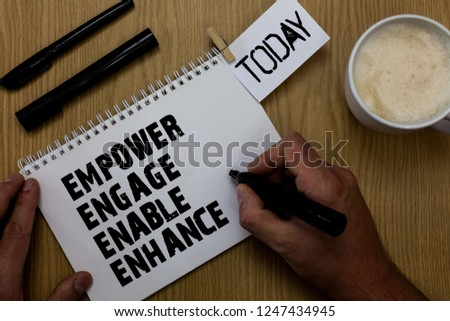 Text sign showing Empower Engage Enable Enhance. Conceptual photo Empowerment Leadership Motivation Engagement Paperclip retain written notepad hand hold marker coffee black pen on woody desk.