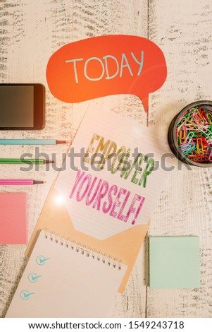 Text sign showing Empower Yourself. Conceptual photo taking control of our life setting goals and making choices Envelop speech bubble smartphone sheet pens spiral notepads clips wooden.