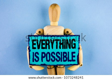 Text sign showing Everything Is Possible. Conceptual photo All you think or dream can become true Optimistic written on Sticky note paper holding by Wooden Robot Toy on the plain background. #1073248241