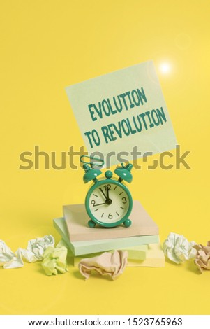 Text sign showing Evolution To Revolution. Conceptual photo adapting to way of living for creatures and huanalysiss Alarm clock sticky note paper balls stacked notepads colored background.