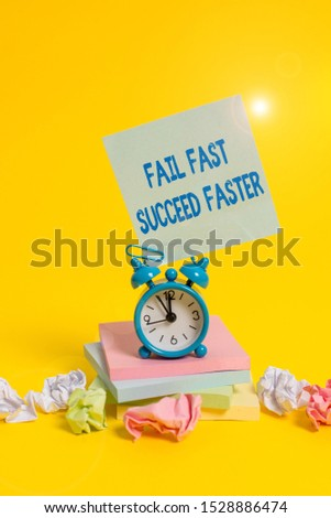 Text sign showing Fail Fast Succeed Faster. Conceptual photo dont give up keep working on it to achieve Alarm clock sticky note paper balls stacked notepads colored background.