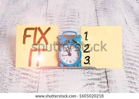 Text sign showing Fix It. Conceptual photo Fasten something securely in a particular place or position To repair Mini blue alarm clock standing above buffer wire between two notation paper.