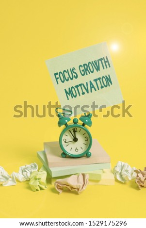 Text sign showing Focus Growth Motivation. Conceptual photo doing something with accuracy increase productivity Alarm clock sticky note paper balls stacked notepads colored background.