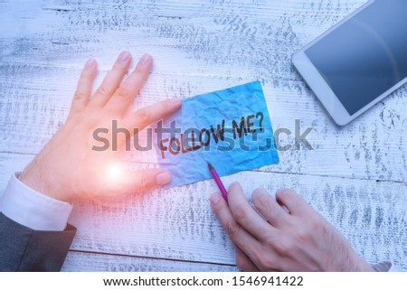 Text sign showing Follow Me Question. Conceptual photo go or come after demonstrating or thing proceeding ahead Hand hold note paper near writing equipment and modern smartphone device. #1546941422