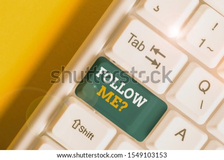Text sign showing Follow Me Question. Conceptual photo go or come after demonstrating or thing proceeding ahead White pc keyboard with empty note paper above white background key copy space. #1549103153