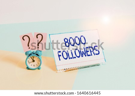 Text sign showing 8000 Followers. Conceptual photo number of individuals who follows someone in Instagram Mini size alarm clock beside a Paper sheet placed tilted on pastel backdrop.