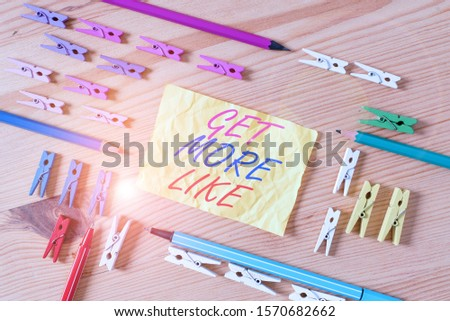 Text sign showing Get More Like. Conceptual photo Thumbs up Hashtags Page Plugin Approvals Followers Colored clothespin papers empty reminder wooden floor background office. #1570682662