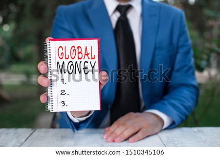 Text sign showing Global Money. Conceptual photo International finance World currency Transacted globally Man holds empty paper with copy space in front of him. #1510345106