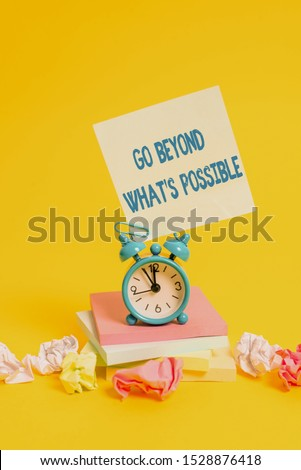 Text sign showing Go Beyond What S Possible. Conceptual photo do bigger things You can reach dreams Alarm clock sticky note paper balls stacked notepads colored background.