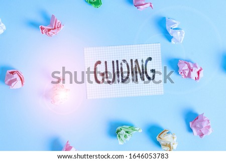 Text sign showing Guiding. Conceptual photo to show someone how to do something difficult Indicate the way Colored crumpled rectangle shaped reminder paper light blue background.