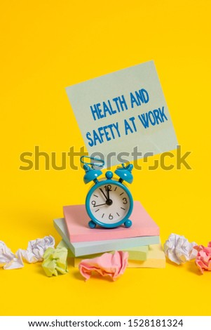 Text sign showing Health And Safety At Work. Conceptual photo Secure procedures prevent accidents avoid danger Alarm clock sticky note paper balls stacked notepads colored background.