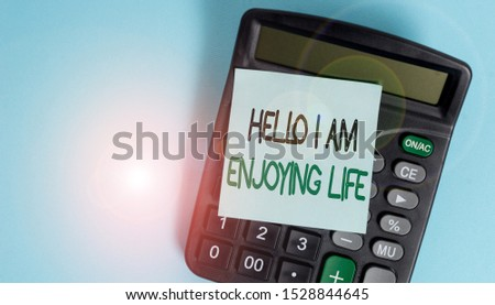 Text sign showing Hello I Am Enjoying Life. Conceptual photo Happy relaxed lifestyle Enjoy simple things Portable electronic calculator device blank sticky note colored background. #1528844645