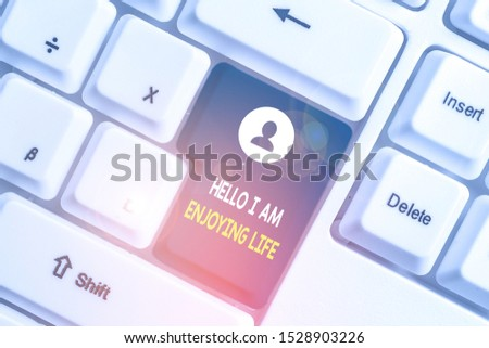 Text sign showing Hello I Am Enjoying Life. Conceptual photo Happy relaxed lifestyle Enjoy simple things White pc keyboard with empty note paper above white background key copy space.