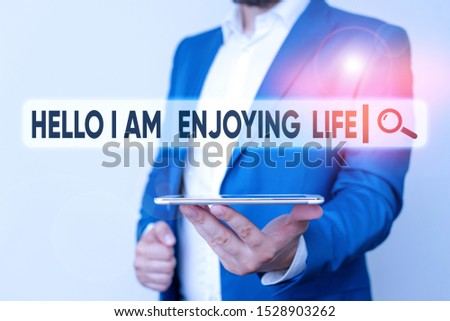 Text sign showing Hello I Am Enjoying Life. Conceptual photo Happy relaxed lifestyle Enjoy simple things Man in the blue suite and white shirt holds mobile phone in the hand.