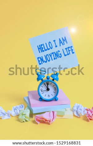 Text sign showing Hello I Am Enjoying Life. Conceptual photo Happy relaxed lifestyle Enjoy simple things Alarm clock sticky note paper balls stacked notepads colored background. #1529168831