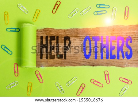 Text sign showing Help Others. Conceptual photo the action of helping someone to do something or assistance Paper clip and torn cardboard placed above a wooden classic table backdrop.