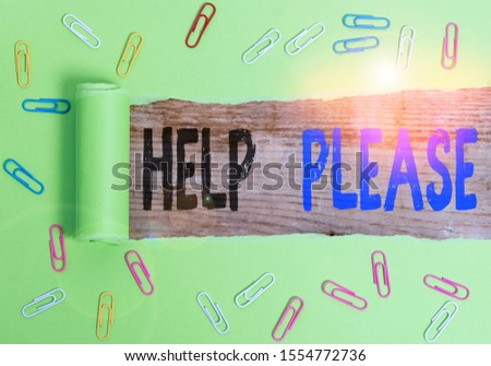 Text sign showing Help Please. Conceptual photo used to make a request or deanalysisd for someone for assistance Paper clip and torn cardboard placed above a wooden classic table backdrop.